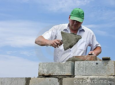 A house builder (bricklayer) at work. He is using his trowel to lay another…