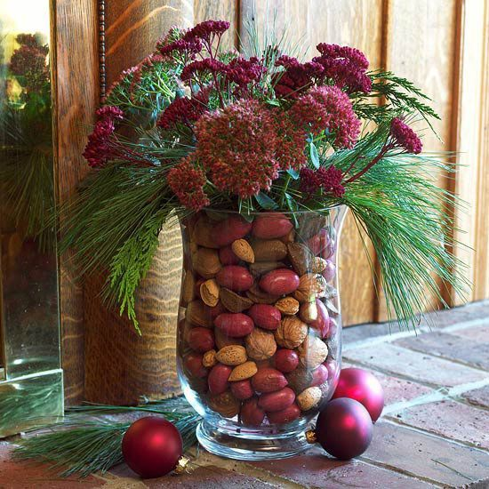 Tuck a small vase inside a larger glass urn and fill the space between the two with mixed nuts. Fill the small vase with water and add fresh flowers or greenery.