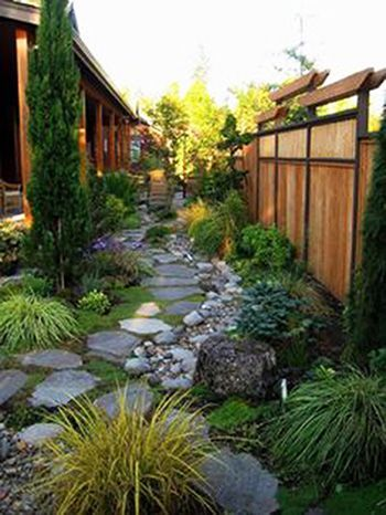 This dry creek bed design is a lot of lusciousness in a small area and shows how, with a bit of creativity, you can turn a narrow outdoor space into an oasis. A simple rock path lined with larger stones and thick greenery lead the way to a quaint seating area where you can enjoy your hard work with a drink in hand.