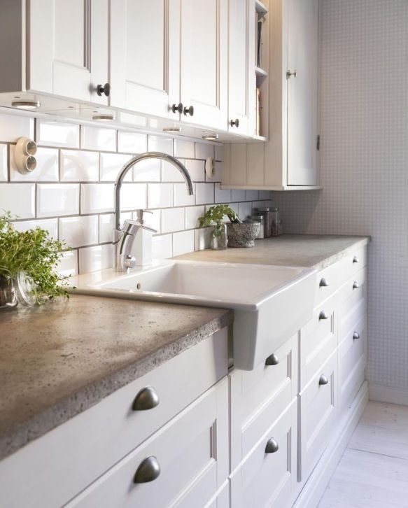 White cabinets, concrete countertops, apron sink ...