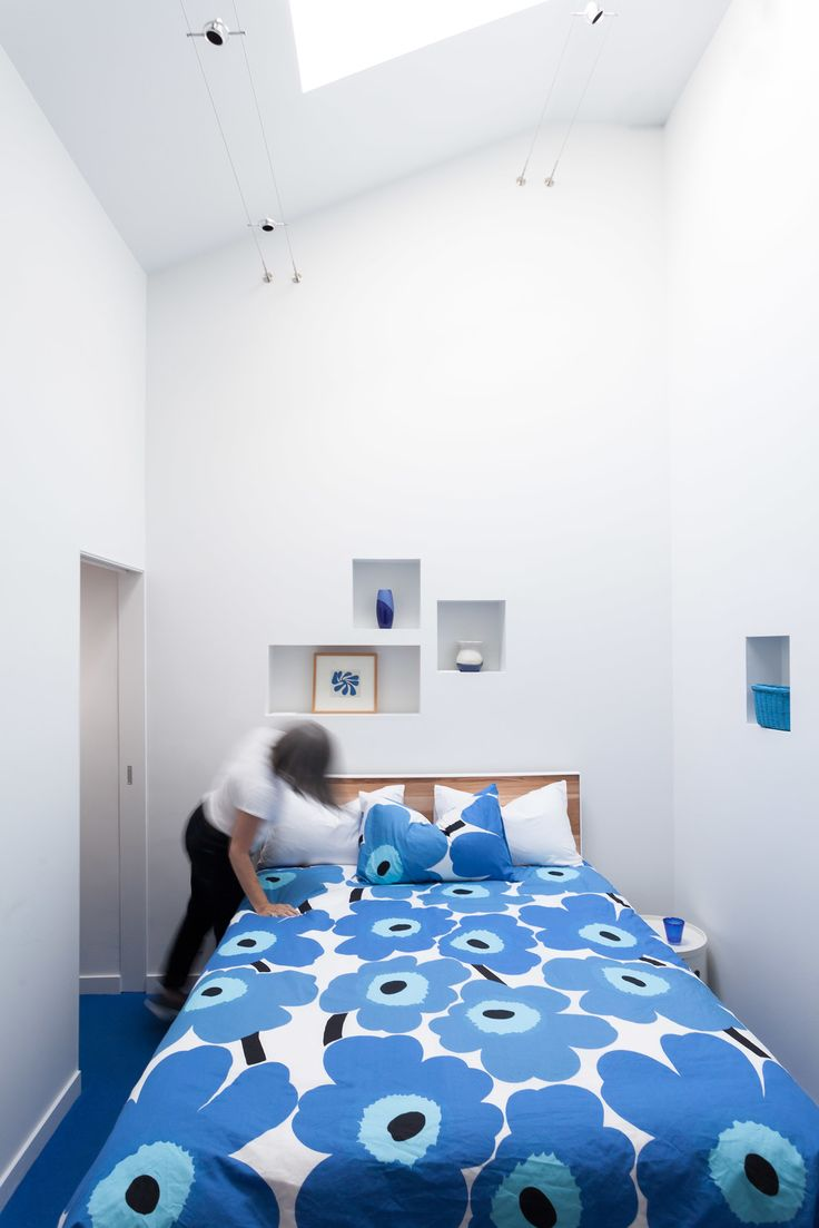 The cut-outs were added into the bedroom walls while the bed is outfitted with one of Marimekko's classic duvet covers.