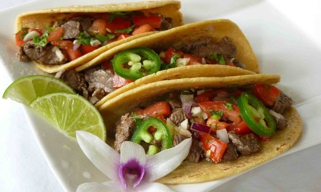 Strips of beef are marinated in lime and pepper, then quickly sauteed, and served in soft corn tortillas with tomatillo sauce and your favorite toppings.