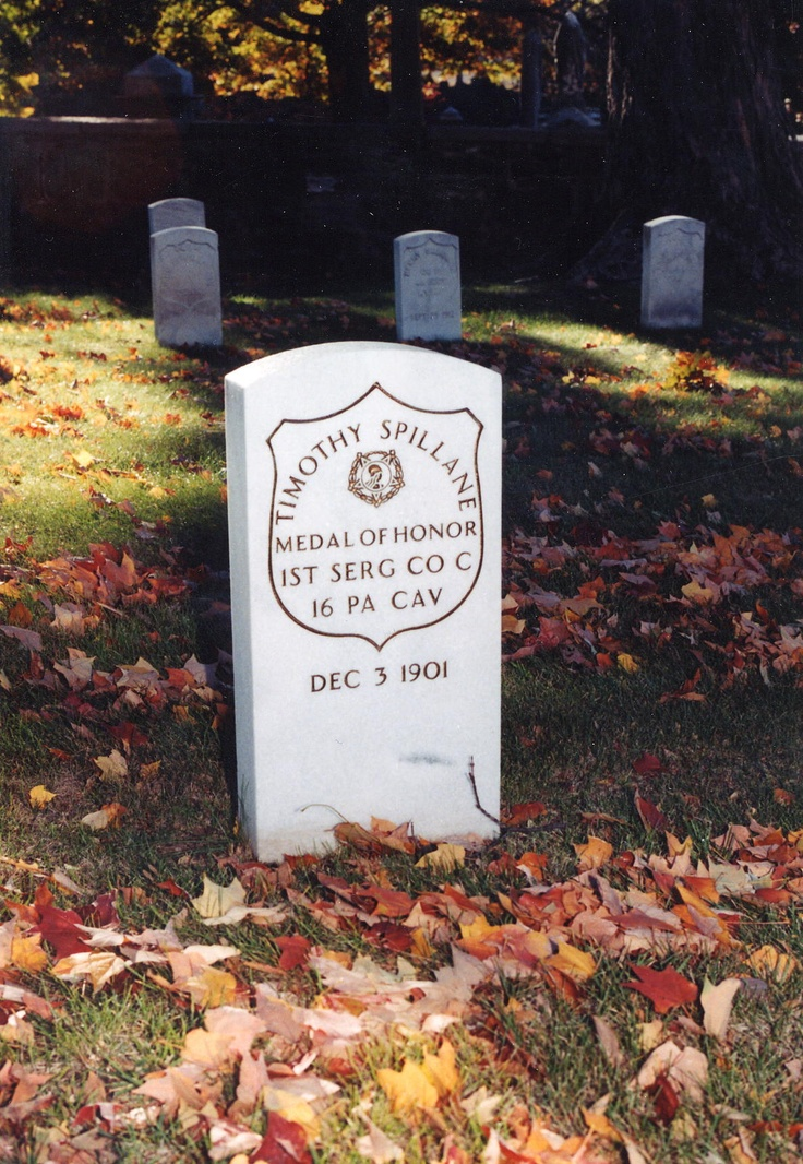 A photo of an upright marker with the name of a medal of honor recipient buried on December 3, 1901. Fall leaves are sprinkled throughout the grounds.