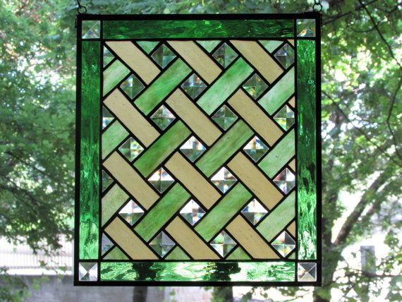 This stained glass panel is made with a basket weave design. The Youghiogheny opalescent stipple glass is woven with green and soft yellow in a 1 pattern with 1 square clear bevels. The border is a green wavy glass with 1 square clear bevels in each corner. The panel is finished with a 1/4 zinc border and a black patina throughout.  Measures approximately 11 1/4 x 12 3/4.