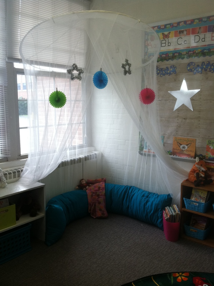 A reading corner with a big pillow and the books are displayed on the shelf next to the big pillow in baskets. Hanging material creates different area for the children. I really like the big pillow and the hanging material. I would add a comfy rug and some more pillows. I would change how the books are displayed if the children needed it.