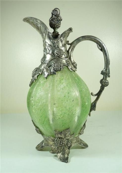 graveyarddirt:    Art Nouveau Pewter Claret Jug, via Ebay  A WMF Art Nouveau Pewter & Texture Green Glass Claret Jug. Dating to the late 19th /early 20th century. With a moulded green glass body with a textured surface. With beautifil Art Nouveau scrolling silvered pewter  mounts cast with fruiting vines. Its underside is stamped 'W.M.F.B, I/O OX', it measures 31cm. high. In very good condition with no damage or repairs. The underside of the lip has a personal engraving with the dates 1876