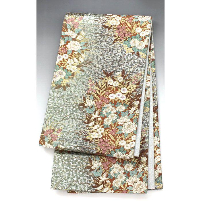 袋帯 茶×銀 白いぼたんや桃の花が綺麗【送料無料】 【中古】【仕立て上がりリサイクル帯・リサイクル着物・リサイクルきもの・アンティーク着物・中古着物】茶色と銀箔の地に、茶色の中には金の葉に白いぼたんや菊、桃の花が入った豪華な袋帯です。  <シチュエーション> 付下げや訪問着など豪華なお着物と合わせていかがでしょうか  <風合> ざらつき感のある手触りのしっかりした生地風合いです。  <状態>  使用感があり、シワや折り目がありますが特に目立つ汚れは無く状態良好ですので、お気軽にお召し頂けます。