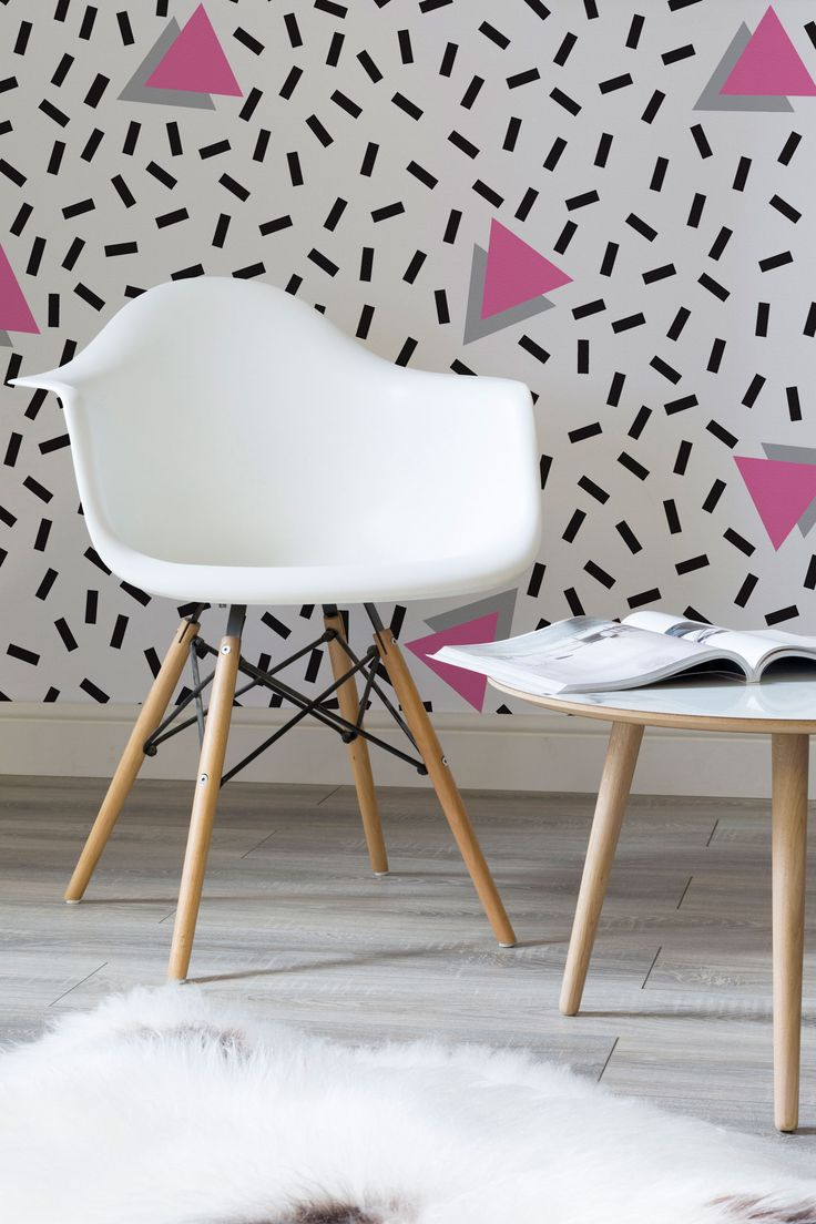 3D pink triangles are scattered amongst sprinkles of bold dashes. Giving a playful yet stylish wallpaper that's taken inspiration from the Memphis movement. Style with contemporary furnishings to offset the 80s vibe.
