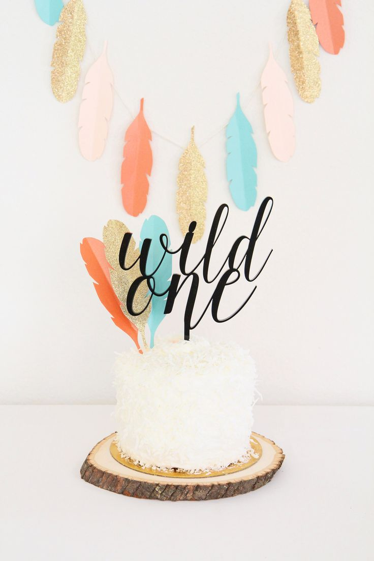 Wild One Tribal 1st Birthday Party   Custom Acrylic Cake Topper from Sweet Paper Shop    Fringy Coconut Cake & Rustic Wood Base   DIY Paper Feather Garland & Cake Decoration   Read about it on our blog!