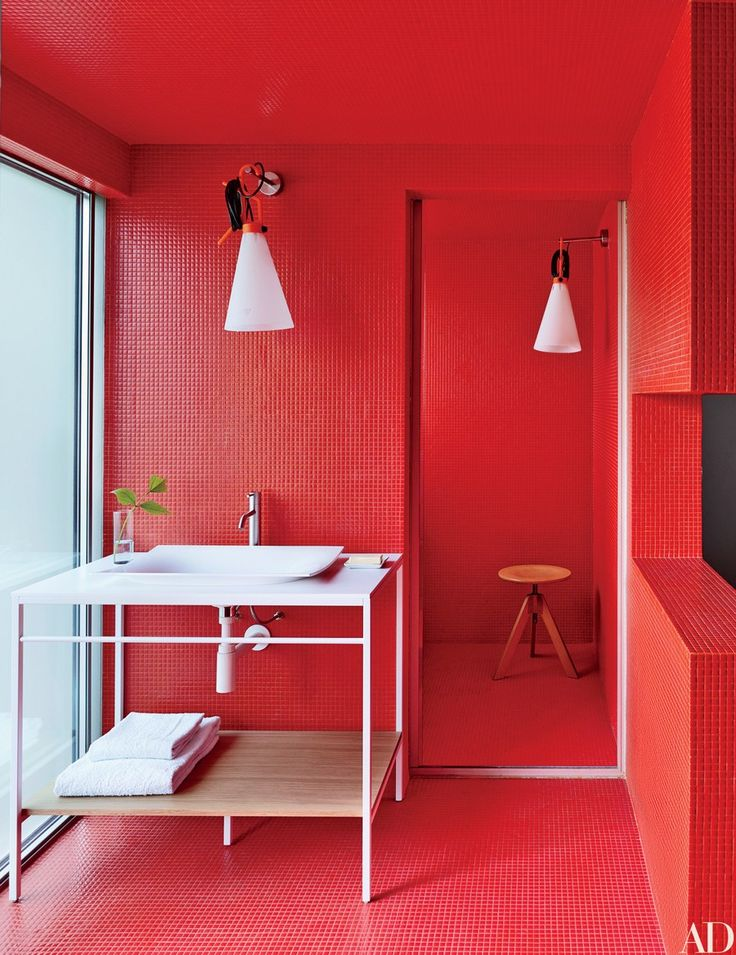 Red Bisazza tile lines a bath of a São Paulo home designed by the Campana brothers; the light fixtures are by Konstantin Grcic for Flos, and the vanity, sink, and fittings are by Antonio Lupi.