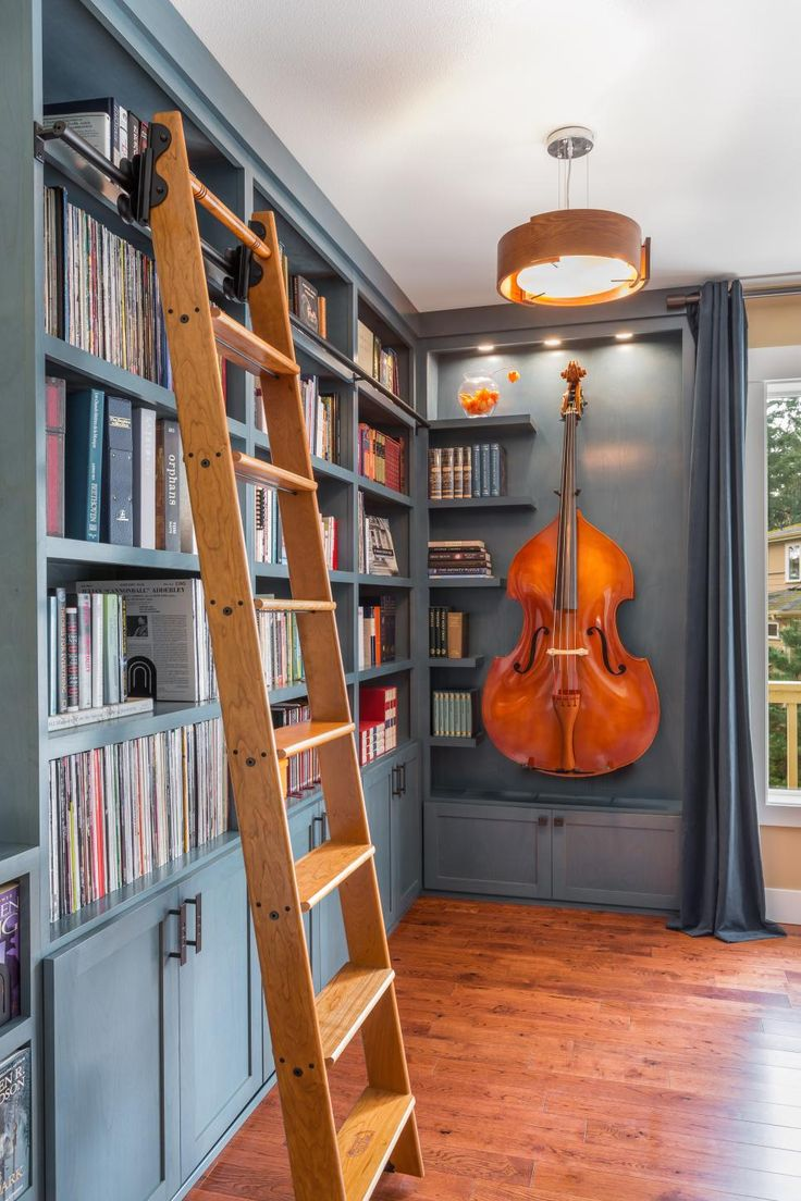 HGTV presents a gorgeous blue home library that once was merely an unused corner in the great room but now serves to display an extensive book and music collection as well as a cello.