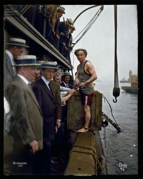 """Harry Houdini steps into a crate at New York Harbor as part of an escape stunt, July 7, 1912."