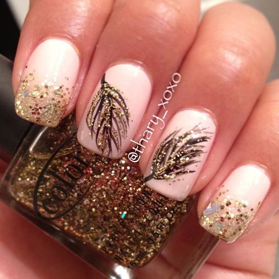 Pink base with feathers on two middle fingers and gold sparkles on tips of index finger and pinky. Nail art design.