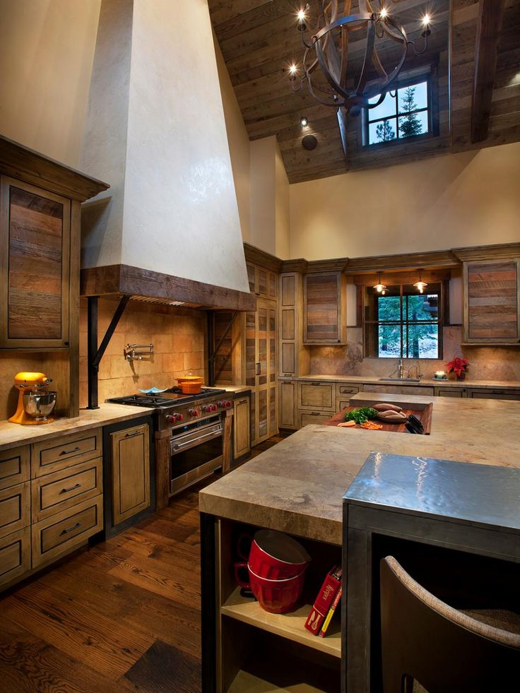 With a pronounced, clean-lined range hood and reclaimed wood accents, this rustic kitchen feels stylish and current. High ceilings and a chandelier give the earthy space a subtle sense of grandeur.