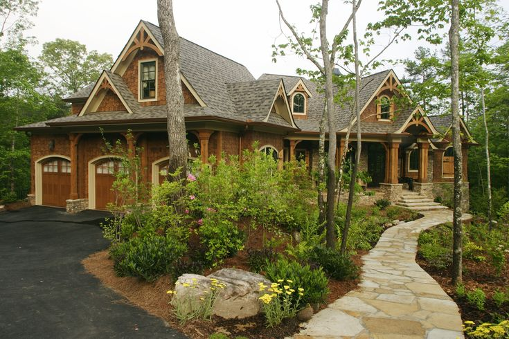 Having a home in the woods where you can relax and enjoy nature is the perfect vacation! This home has a light tan stone walkway that leads to an earthy and charming cottage. There is a three-car garage with arched doors. Click to see how much it costs to install a garage door.