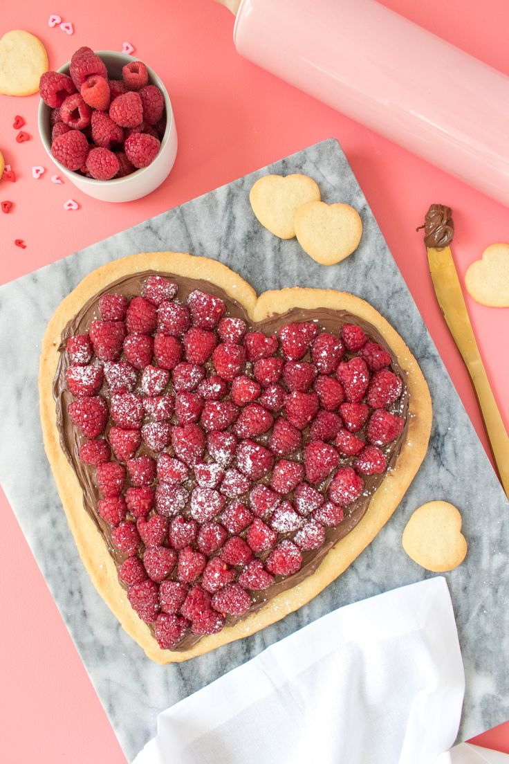 This Valentine's Day make a heart-shaped dessert pizza topped with Nutella and your favorite berries. This easy-to-make recipe features a sugar cookie crust and kid-friendly although adults will love it too.