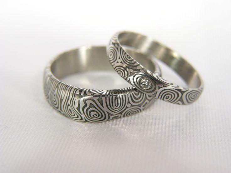 Pár snubních prstenů Wavereyes z damascénské oceli Do detailu zpracované šperky z damascénské oceli, varianta s diamantem. V nabídce též varianta bez kamene či s kamenem dle volby zákazníka. Velikost diamantu je , vzor eyes, hluboký lept.