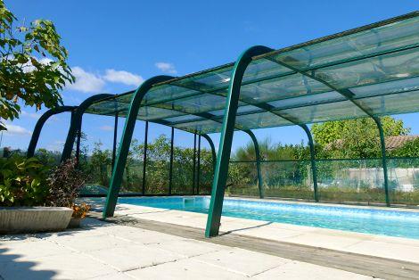 Abri haut de piscine fixe de couleur verte s'harmonise parfaitement avec son environnement verdoyant !
