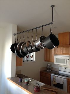 great pot and pan rack; could use curtain rod on ceiling with shower hooks as hangers. above the bar is the perfect place to not block cupboards or get in the way.