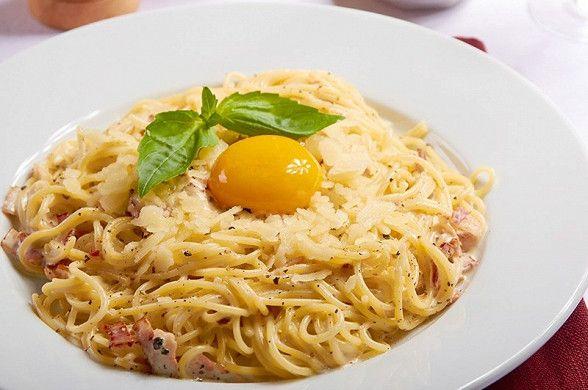 Поставьте кипятиться подсоленую воду для пасты. Нарежьте бекон широкими полосками. Раздробите перец плоской стороной ножа. Куриные яйца тщательно вымойте с мылом.