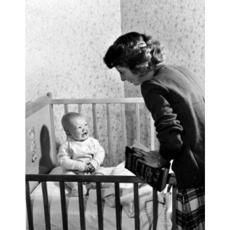 Mother standing at crying baby boy sitting in crib Canvas Art - (18 x 24)