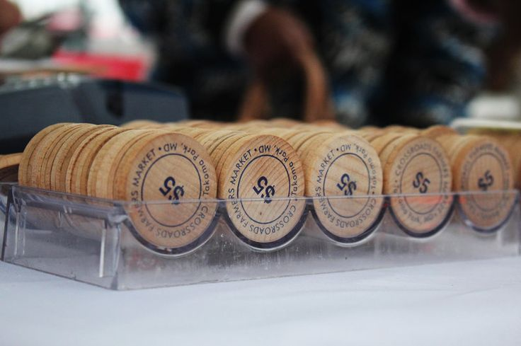 """These wooden tokens are handed out to shoppers who use SNAP benefits to purchase fresh produce at the Crossroads Farmers Market near Takoma Park, Md. Customers receive tokens worth twice the amount of money withdrawn from their SNAP benefits card — in other words, they get """"double bucks."""""""