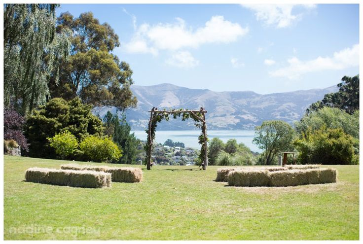 An outdoor rustic wedding ceremony setting on the rolling lawn of Vernon Lodge, with a glimpse of the distant hills and nearby sparkling harbour. Akaroa, New Zealand.