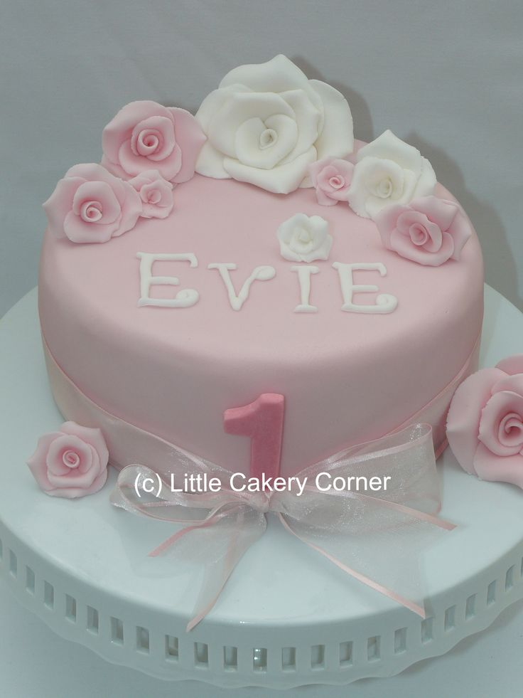 A beautiful little girl's 1st birthday cake.  This pale pink iced single-tier cake has been decorated with delicate baby pink roses and white roses, finished with a pretty chiffon pink bow and a number one.  This could be adapted from a first birthday cake to suit any age, including an 18th, 21st - or evening a christening, wedding cake or engagement.  It would look gorgeous in any pastel colours theme and the design could be applied to multiple-tiers.