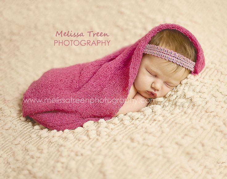Beautiful newborn baby girl sleeping sweetly on beige popcorn texture blanket wrapped in pink baby prop