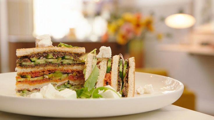 Dit is een Griekse BLT sandwich. Het is een typisch Engelse clubsandwich met bacon, tomaat en sla, gecombineerd met drie soorten tapenade.
