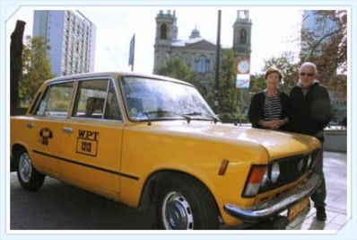 Yellow retro fiat with Warsaw in the background