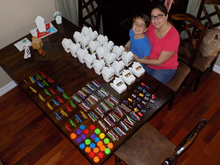 Jay helped me prep the goodie boxes for his friends.  Everyone got a Chinese take out box with ninja eyes on the front with the following contents: a ninja (Party City), a glow in the dark flute (Dollar Tree), a sticky throwing ball (also from Party City, because I couldn't find any ninja throwing stars),  and three packages of sixlet candies - in Ninjago colors of course!