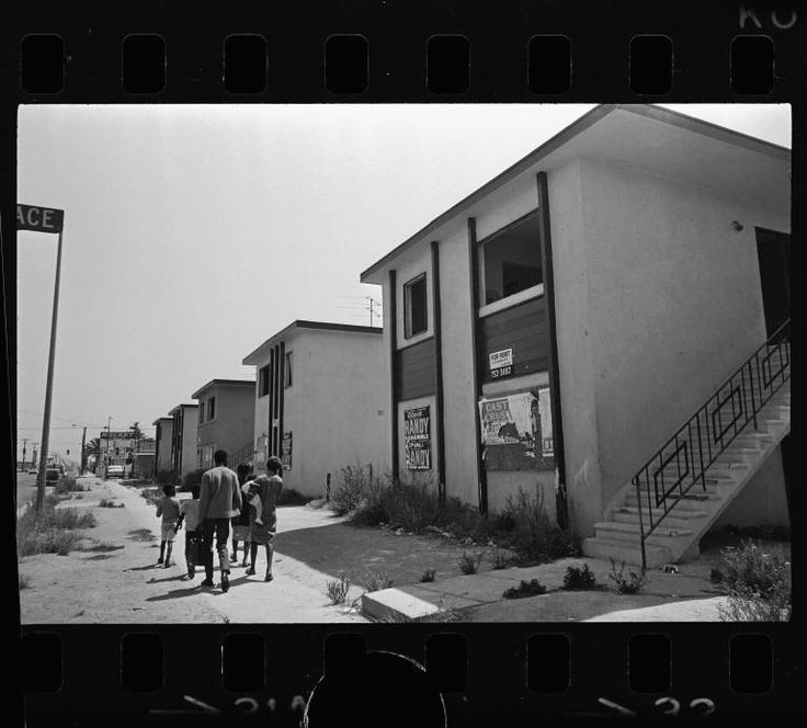 """""""Abandoned apartments in Watts, Los Angeles (Calif.)""""  Moving on--Negro family passes row of vacant apartment buildings in Watts, where those who can are joining the Negro shift westward.  Los Angeles Times (Firm), Publisher, July 21, 1967. Image from UCLA, Special Collections, Young (Charles E.) Research Library."""