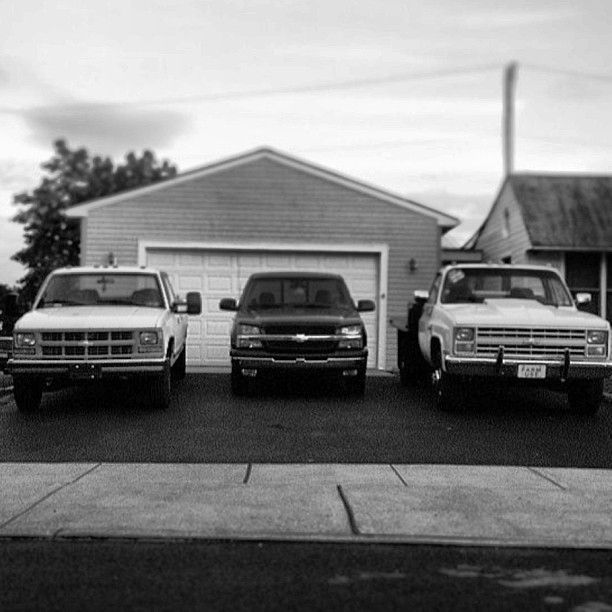 lifted Chevy trucks front of garage
