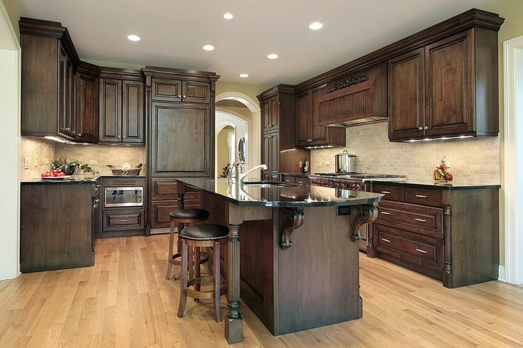 Truly dark wooden cabinets and island, along with black countertops, work with the light natural flooring and tile backsplash in this contrasting kitchen.