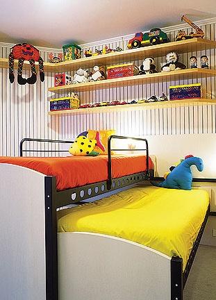 """As camas deslizantes correm em trilhos fixados em um painel na parede. De dia, uma """"se esconde"""" sob a outra, liberando espaço para brincadeiras. À noite basta puxar uma delas"""