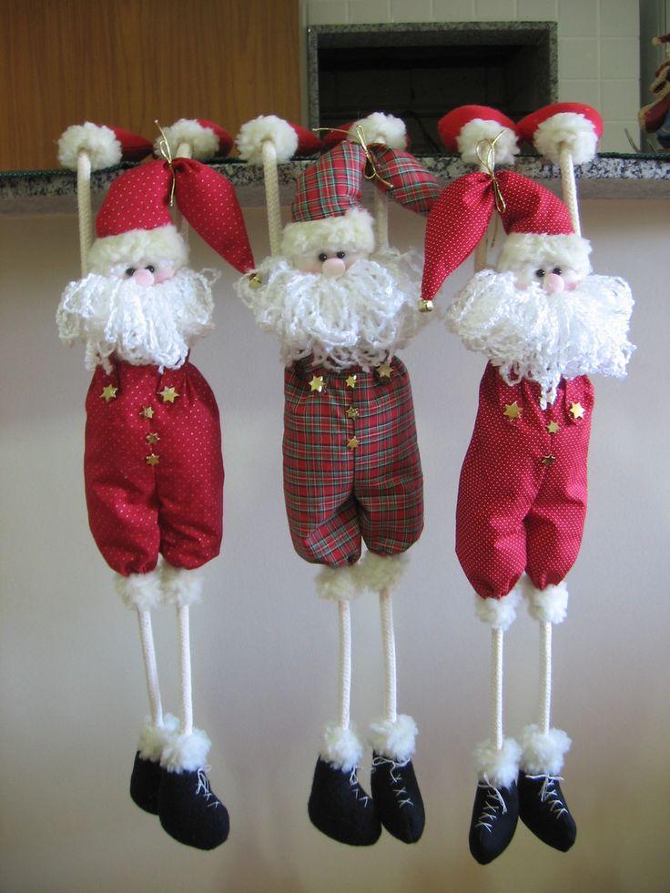 Papai Noel fica pendurado pelas mãos. Dentro das mãos tem um peso que permite que ele fique firme. Ideal para enfeitar lugares onde se tem pouco espaço, como uma estante, já que ele fica pendurado. Disponível 1 unidade na cor vermelha com barba de lã branca e 1 unidade em verde xadrez com vermelh...