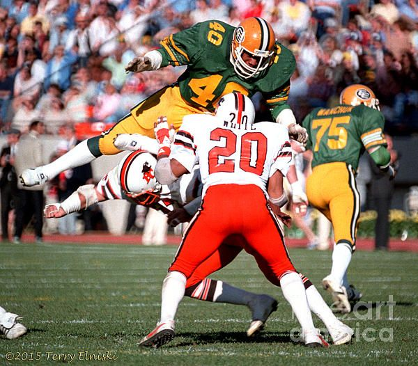 Action photograph taken of Edmonton Eskimos James Parker #40, being blocked on this punting play by a couple of B.C. Lions ball players, 1982. PHOTOGRAPH BY TERRY ELNISKI