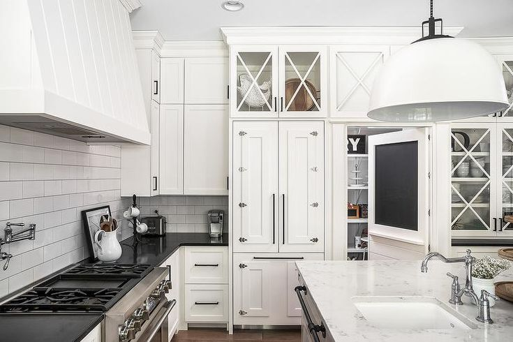 A kitchen refrigerator is concealed with white shaker cabinetry accented with vintage latch hardware complimenting the oil rubbed bronze on perimeter cabinetry.