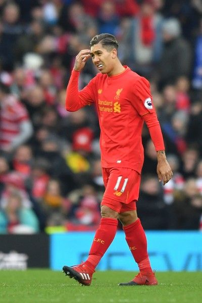 Liverpool's Brazilian midfielder Roberto Firmino reacts after Swansea scored their third goal during the English Premier League football match between Liverpool and Swansea City at Anfield in Liverpool, north west England on January 21, 2017. / AFP / Anthony DEVLIN / RESTRICTED TO EDITORIAL USE. No use with unauthorized audio, video, data, fixture lists, club/league logos or 'live' services. Online in-match use limited to 75 images, no video emulation. No use in betting, games or single…