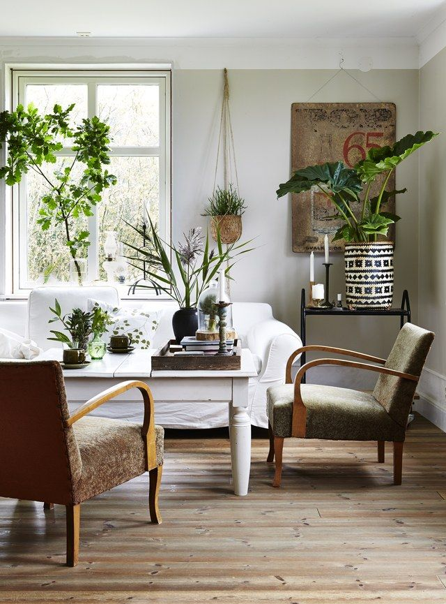 """""""Naturally occurring color combinations found in landscapes, flora, and fauna are often the most pleasing matches,"""" writes Lake. Using natural shades like whites, soft grays, and pale browns give florals a serene and calming backdrop. This Scandinavian-inspired living room brings in textures like a woven basket, linen upholstery, and a touch of black metal to add a touch of interest."""