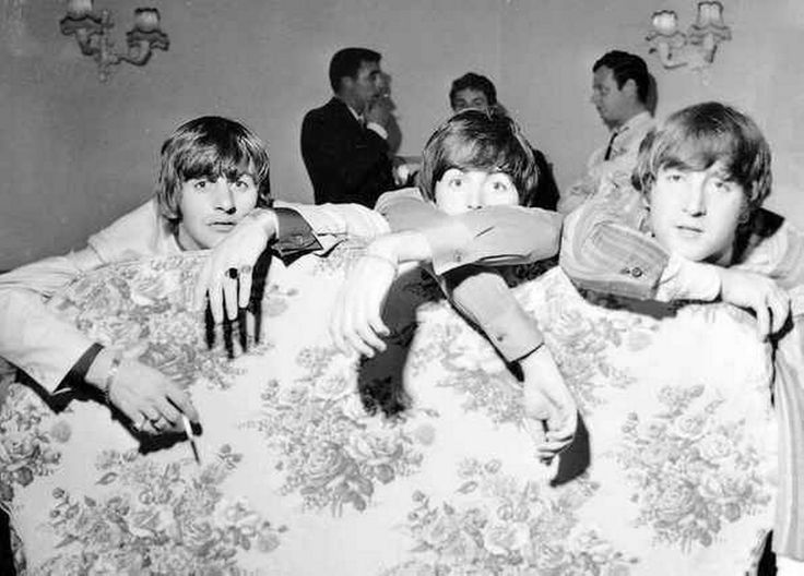 19th July 1964. Ringo, Paul and John lounge about on a sofa in Blackpool while Derek Taylor, Neil Aspinall and Brian Epstein talk in the background.