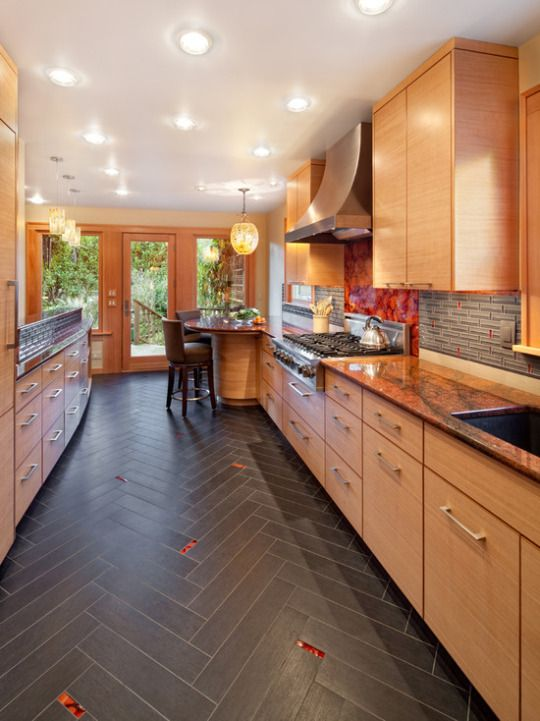 Extremely detailed kitchen - dark hardwood floor with red accents to compliment the back splash tile with red accents over the cooktop, rich wood bamboo tones and lighting  #home #remodel #kitchen #bathroom #interiors www.jimhicks.com