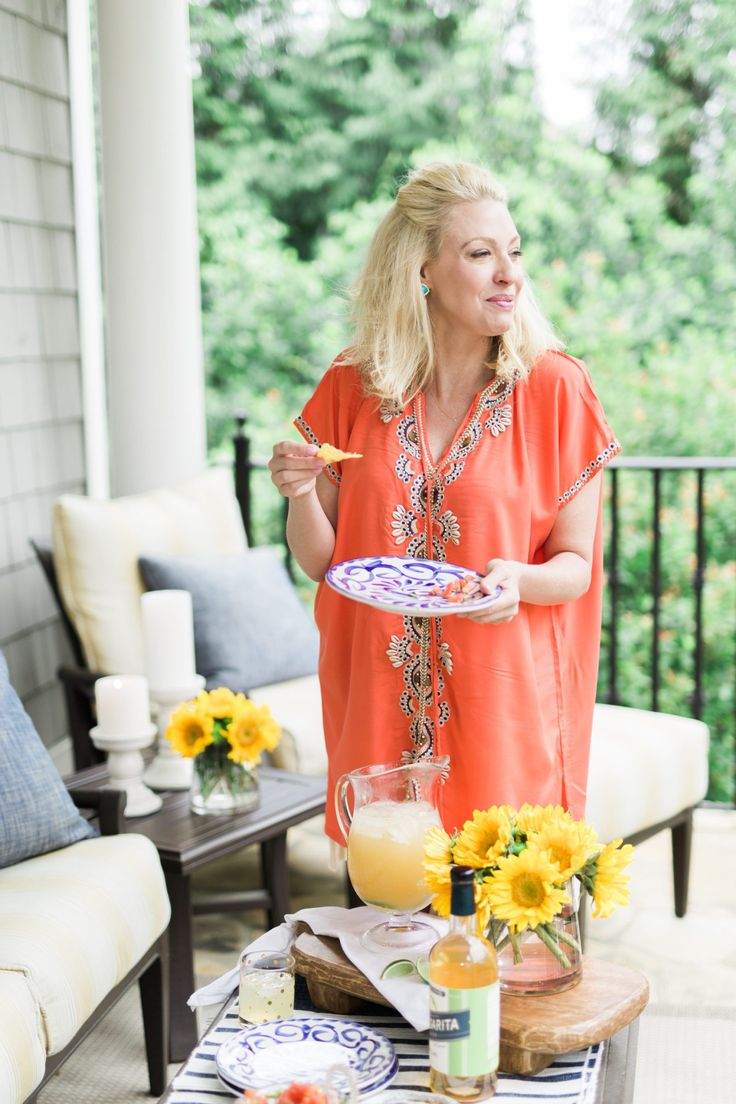 Cindo de Mayo patio party with coral bathing suit cover up and yellow sunflowers on blue and white table setting.