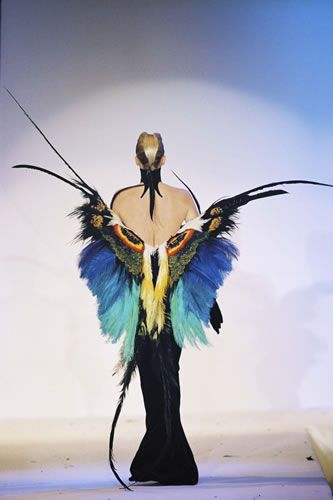 "Thierry Mugler's ""Butterfly"" dress in black velvet sheath with butterfly wings made from multicolored feathers from the ""Les Insectes"" Haute Couture collection. SS97"