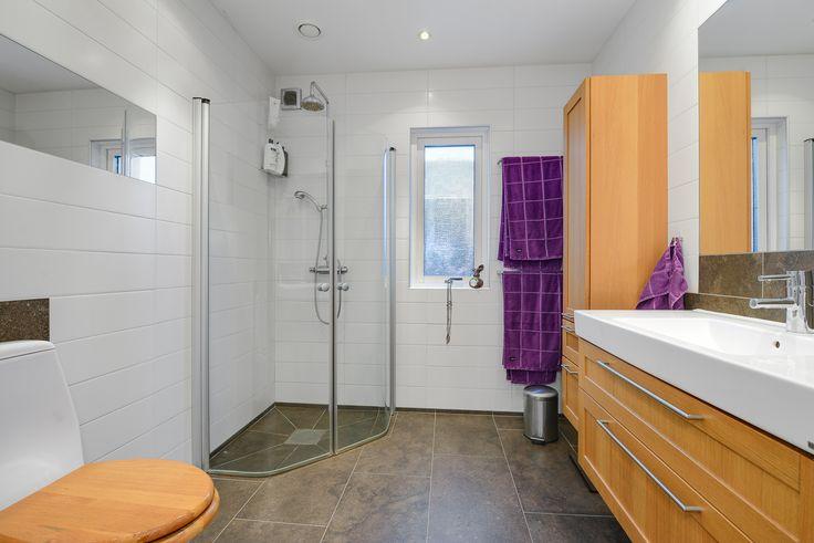 Ljust badrum med fönster, reflekterande speglar och spottar i tak