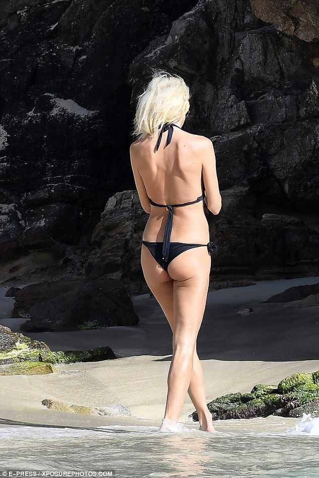 Peachy!The 42-year-old Swedish model and actress slipped into a simple yet stunning black two-piece as she cavorted in the sand on the idyllic shores