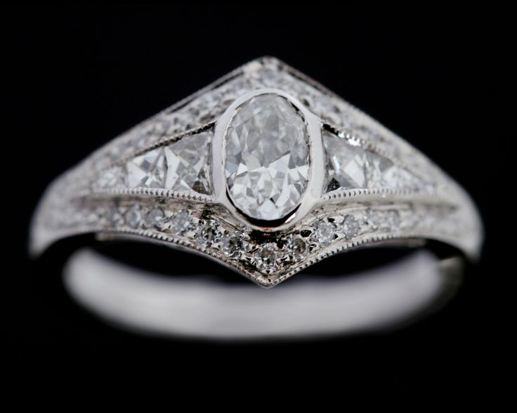 A mixed brilliant cut Diamond surrounded by old cut and French cut diamonds in 18 carat white gold