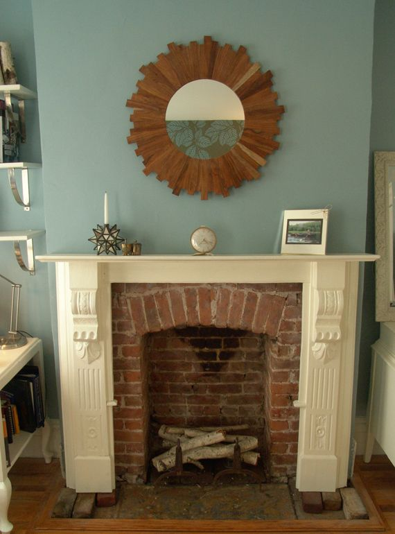I love the old brick framed by the white wood mantel!