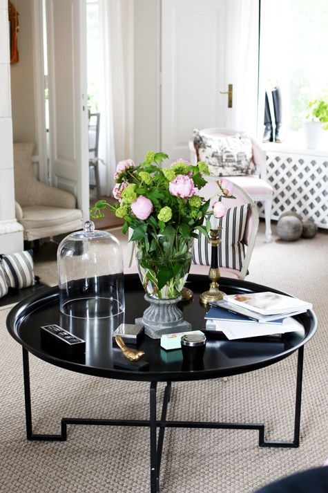 Black coffee table decorated with fresh flowers and golden accents, beautiful living room